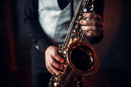 Jazz man hands holding saxophone closeup Stock Photo