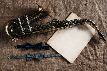 alloys: Saxophone, notes and bowtie on canvas background