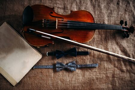 cellos: Violin, fiddlestick, notes and bowties closeup