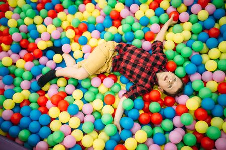 Little boy lying in a pile of colorful balloons Foto de archivo