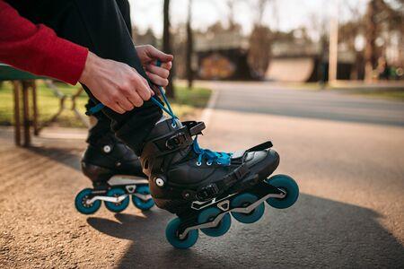skate park: Roller skater sitting on bench and lace up skates Stock Photo