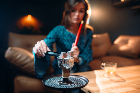 Young woman holds coal with tongs, smoking hookah 스톡 콘텐츠