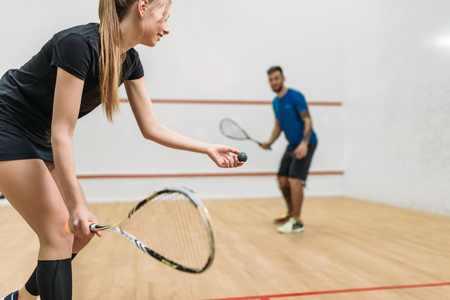 Couple play squash game in indoor training club Foto de archivo