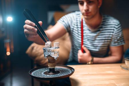 стиль жизни: Молодой человек с щипцами разжигает уголь в кальян-баре