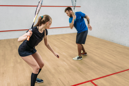 Couple with squash rackets, indoor training club Stock Photo