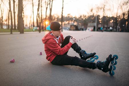 rollerskater: Roller skater sitting on asphalt in city park Stock Photo