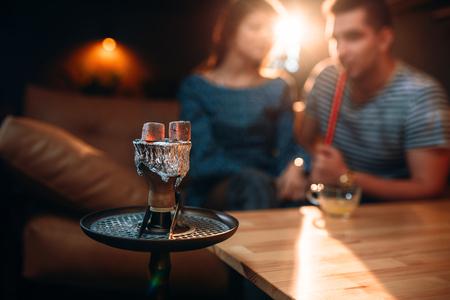joven fumando: Rojo-caliente de carbón en cachimba en club nocturno