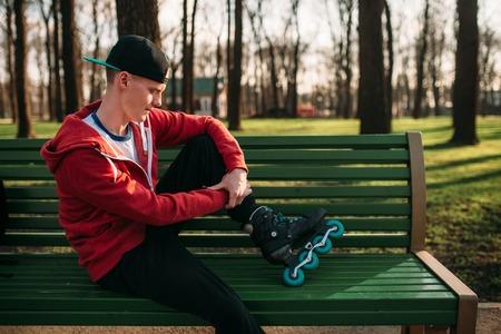 rollerskater: Roller skater posing on the bench in skates Stock Photo