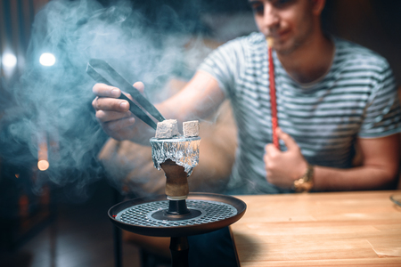 Young man with tongs kindle the coal at hookah bar 스톡 콘텐츠