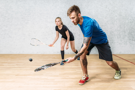Couple with squash rackets, indoor training club 스톡 콘텐츠