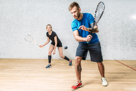 Couple with squash rackets, indoor training club Фото со стока