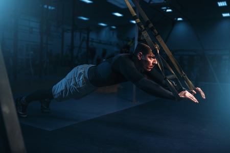 Sportsman on training,endurance workout with ropes