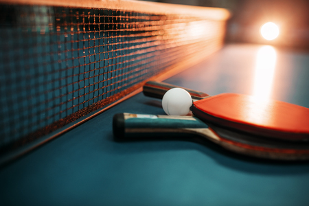 Two tennis rackets and ball against net on table Stock Photo - 80759859