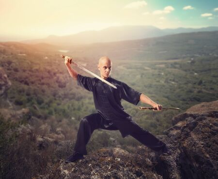 finesse: Wushu master with sword, meditation on mountain Stock Photo