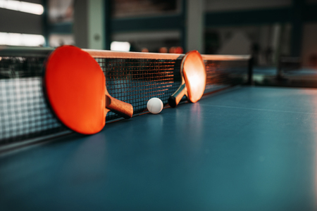 Two tennis rackets and ball against net on table Stock Photo