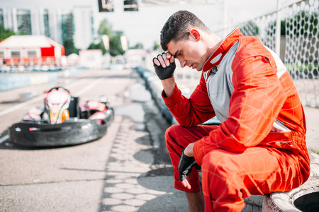 Karting racer sits on a tire, outdoor kart track Stock Photo