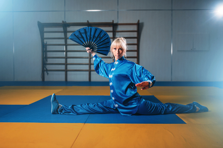 finesse: Female wushu master exercise with fan, martial art