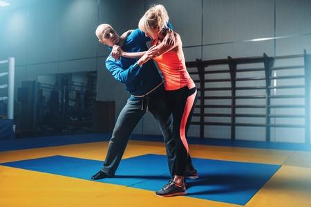 Vrouw vecht met de man op zelfverdedigingstraining