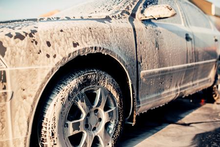 Wet vehicle in foam, automobile in suds, car wash
