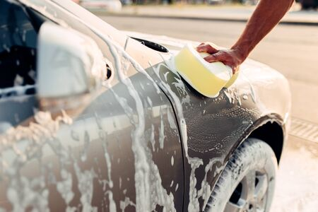 Male hand rubbing the car with foam, carwash Reklamní fotografie