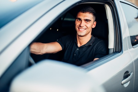 Happy male driver in car, advertising concept