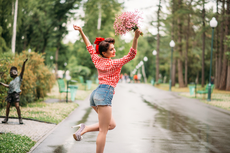 Pinup girl with bouquet of flowers, retro fashion Stock Photo