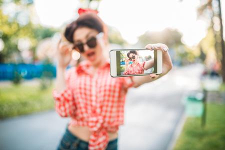Pin up girl in sunglasses, selfie shot in park Imagens