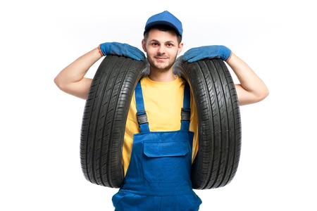 Tire service worker in blue uniform holds car tyre Reklamní fotografie