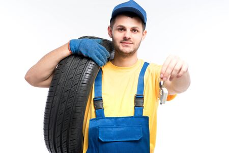 Worker in uniform holds tire and car keys in hands Reklamní fotografie