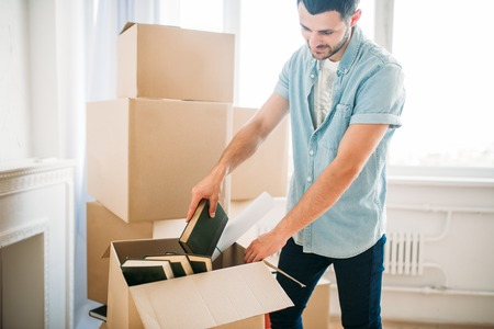 Young man unpacking cardboard boxes, housewarming Stock Photo