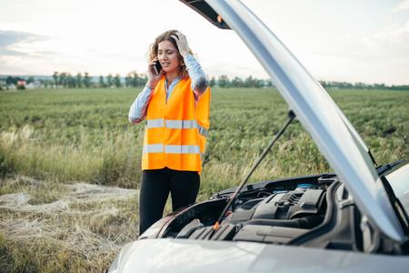 Girl in reflecting vest with phone, broken car Stock Photo