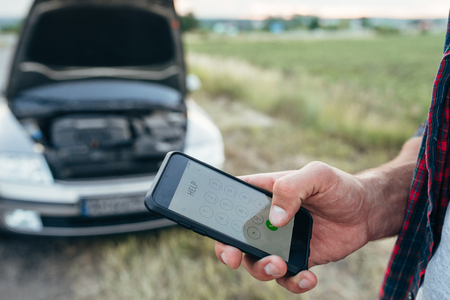 Male person hand with phone, broken car