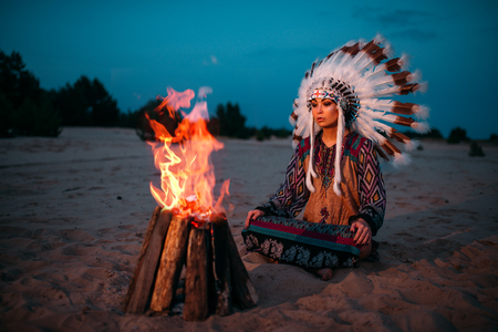 Young American Indian woman against fire Stockfoto