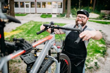 master: Mechanic adjusts the bicycle handlebars and brakes Stock Photo