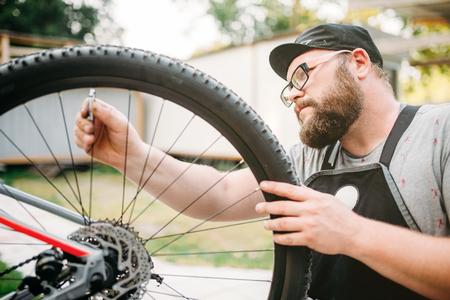 master: Bicycle mechanic in apron adjusts bike spokes