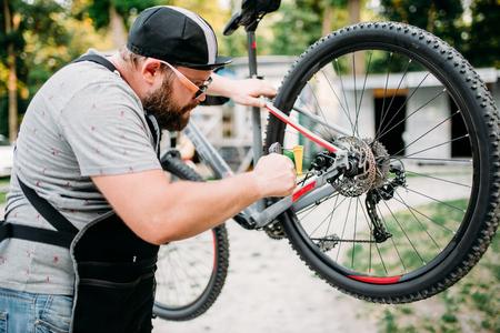 Bicycle mechanic adjusts back disk brakes Stock Photo