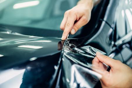 Le mani del lavoratore installano la pellicola di protezione della vernice dell'automobile