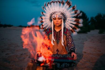 Indianermädchen gegen Lagerfeuer, Schamane
