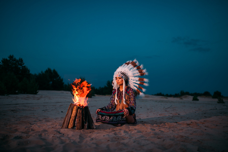 Young American Indian woman against fire Imagens