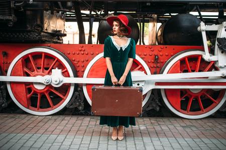 Woman with suitcase against steam locomotive Banco de Imagens