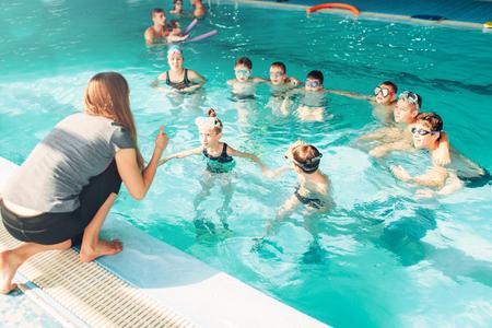 teaches: Instructor teaches children how to swim