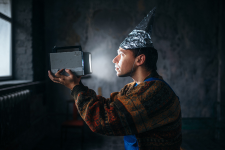 Paranoid man in tinfoil cap, mind protection, UFO