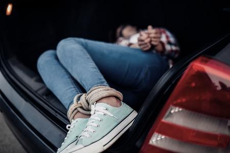 Female victim in car trunk, maniac concept