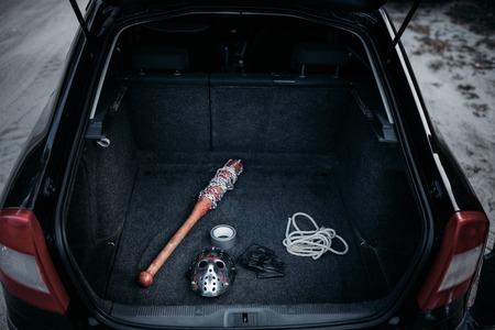 Psycho man instruments in opened car trunk, maniac