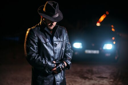 Maniac in black leather coat and hat, back view