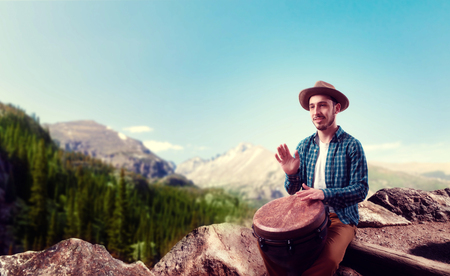 Drummer with wooden drums plays on top of mountain