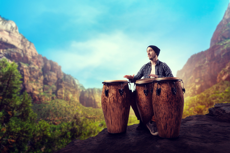 Drummer with wooden drums plays in desert valley Stock Photo
