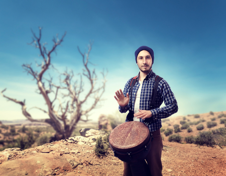 Drummer plays on wooden bongo drums in desert