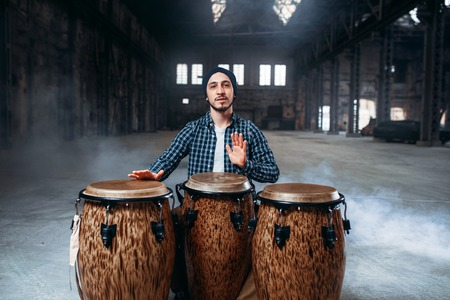 Male drummer plays on wooden drums in factory shop