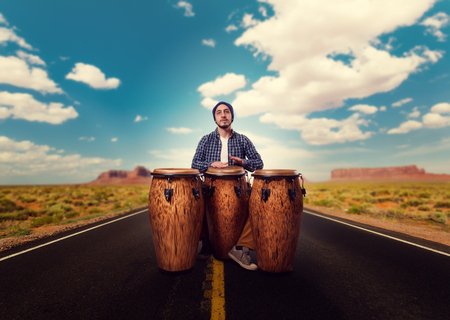 Drummer with wooden drums plays on desert road Stock Photo